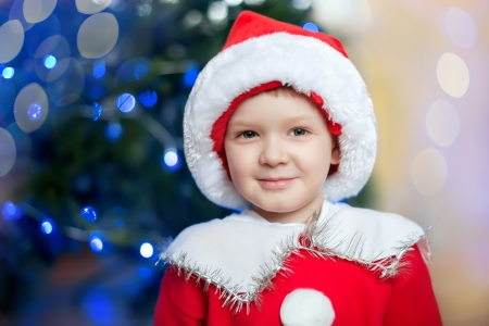 The little boy in a cap of Santa Claus in front of a blurred decorated tree Stock Photo - 16637310