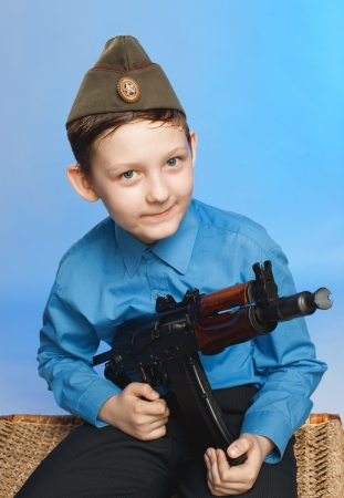 the boy keeps the weapon in a military cap