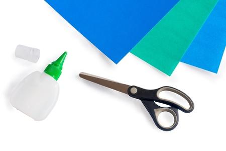 Tijeras, pegamento y papel sobre un fondo blanco