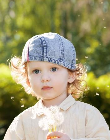Beautiful little curly girl blowing dandelion,vertical shot Stock Photo