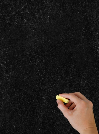 Blackboard. The hand writing with chalk.  Vertical shot. Stock Photo - 17111947