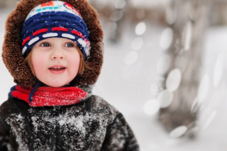 Portrait of the charming child, surrounded by snow with snow covering her clothing