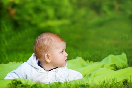 Beautiful little baby lying on the grass in the park photo