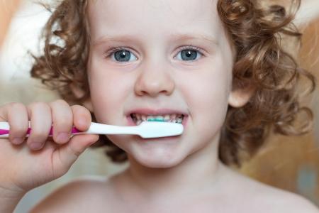 Ni�a cepill�ndose los dientes, retrato del primer Foto de archivo