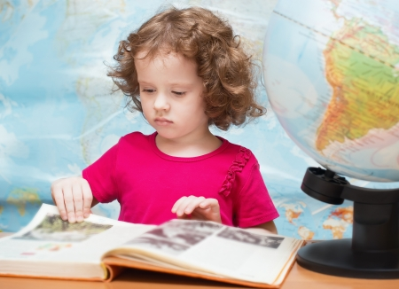 little girl in a red dress is reading a book Stock Photo