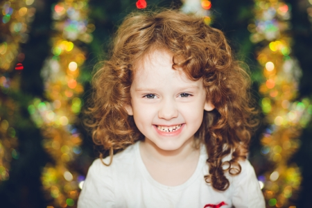 Beautiful little girl looking at the camera and smileson the background of of the Christmas tree