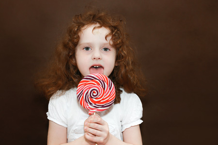sweetness: Girl holding a big lollipop, toned photo on brown background  Stock Photo