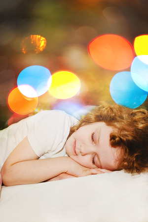 Little girl is sleeping. Against the background of the rainbow bokeh. photo