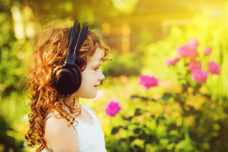 Little girl listening to music on headphones in a summer park.  photo