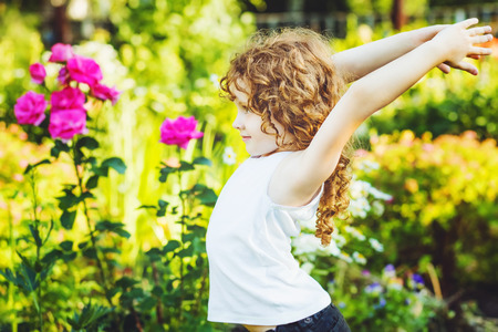 Little girl doing yoga in the summer park. Healthy lifestyles concept. Stock Photo