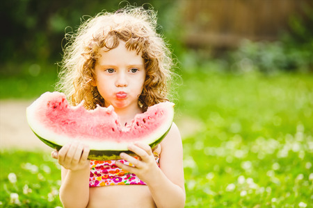 Curly little girl eating watermelon in summer park.  photo