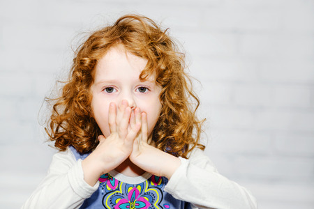mistake: Little girl covering her mouth with her hands. Surprised or scared. On the light background indoors.