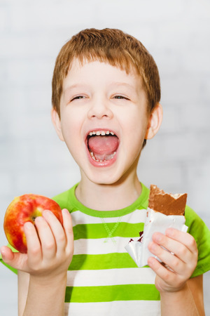 Child chooses chocolate or apple on a light background in the studio. Stock Photo