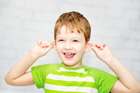 Happy little boy, pulling himself on the ears  and stuck out his tongue.
