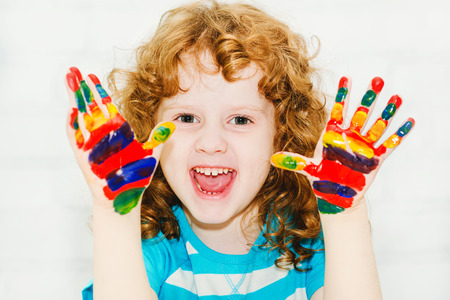 Happy little curly girl with hands in the paint on a light background. Stock Photo