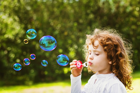 blowing bubbles: A little girl blowing soap bubbles, closeup portrait beautiful curly baby Stock Photo