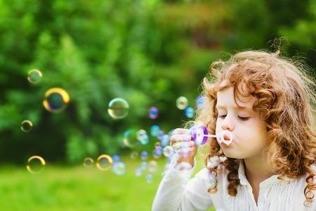 Een klein meisje blaast zeepbellen, close-up portret mooi krullend kindje Stockfoto