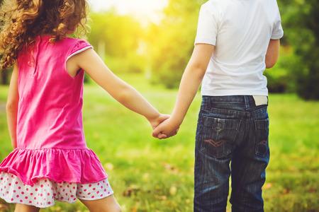 children holding his hand in summer park outdoor. photo