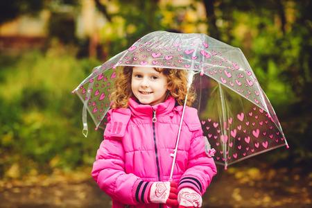 gaily: Little girl hiding under an umbrella from the rain.
