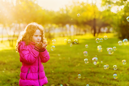 A little girl blowing soap bubbles Stock Photo