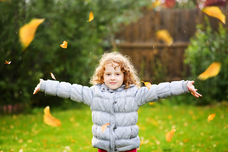 gleeful: Happy little girl throws the autumn leaves in the air. Stock Photo