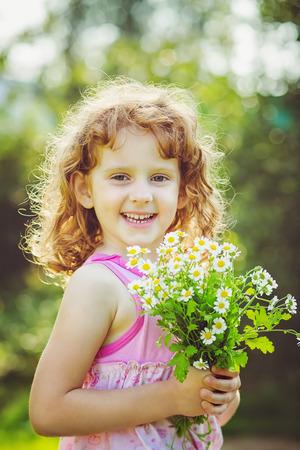 Ni�o feliz en un campo con un ramo de margaritas. Tonificaci�n foto. Foto de archivo