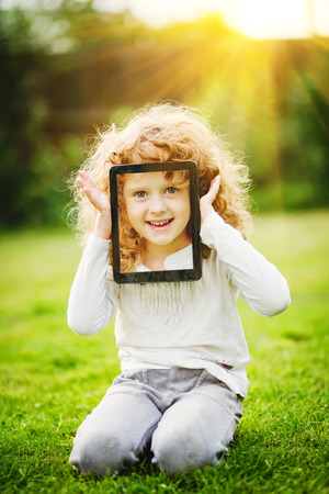 Little girl sitting on the grass and holding tablet pc. photo