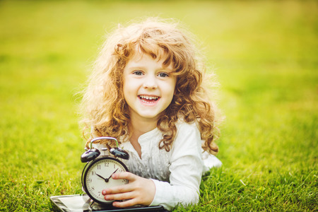 back in time: Girl lying on the grass and holding alarm clock.