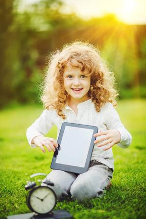 Ni�a que se sienta en la hierba y la celebraci�n de Tablet PC. Foto de archivo