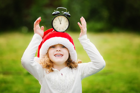 Little girl in Santa hat with clock have a Christmas. Stock Photo