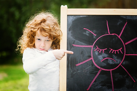 Little girl dissatisfied points on the board with a picture. Sad sun on a blackboard.