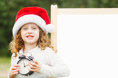 Little girl in Santa hat with clock. Girl at blackboard.  Place for your text. photo