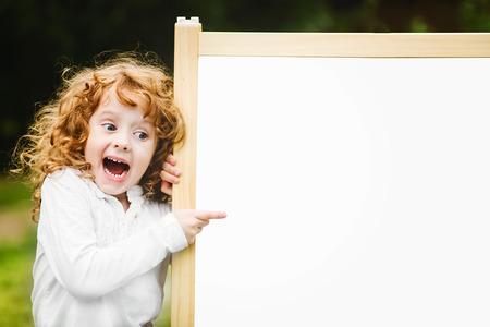 Enfant surpris choqué et heureux avec tableau noir de l'école. Banque d'images