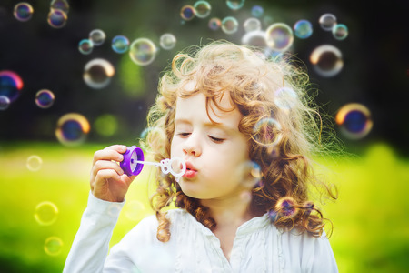 A little girl blowing soap bubbles, closeup portrait beautiful curly baby. Stock Photo