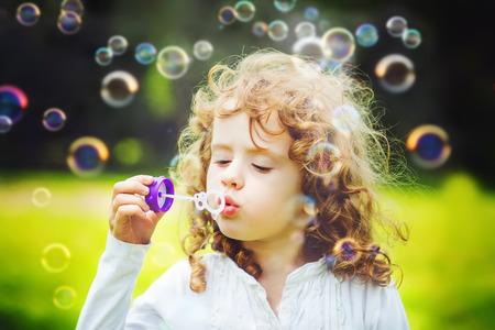 Een klein meisje blaast zeepbellen, close-up portret mooi krullend baby.
