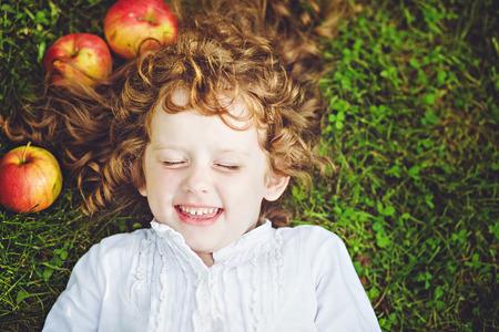 La muchacha rizada encuentra en la hierba y sonriente
