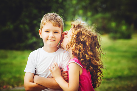 niños platicando: Poco niño y niña susurra.