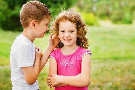 El ni�o susurra un secreto en un o�do a la chica.