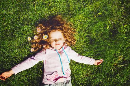 곱슬 소녀 사진 토닝 잔디와 미소에 놓여있다.