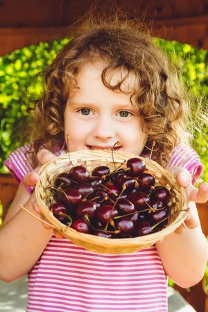 Ni�a hermosa que sostiene una cesta de cerezas dulces.