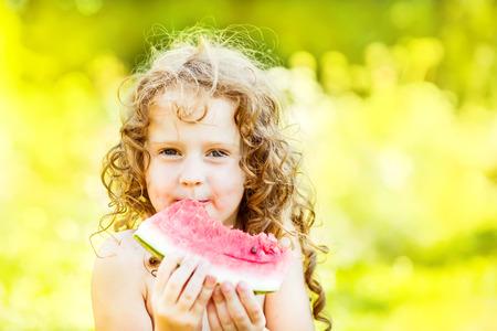 Happy little girl eating watermelon  in summer park. Instagram filter. Stock Photo