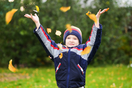 Happy boy throws the autumn leaves in the air. Stock Photo