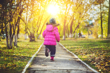 Little girl in a red jacket, running away the road in the autumn park.