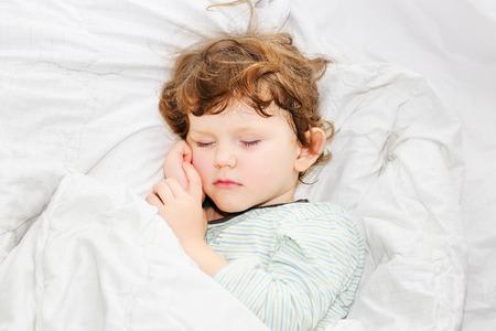 甘い子がベッドで寝ています。