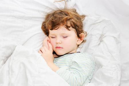 Sweet child sleeping  in bed. Stock Photo