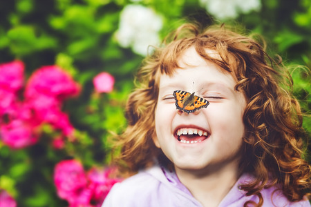 reir: Muchacha de risa con una mariposa en su nariz. Foto de archivo