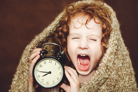 Curly girl  yawn and holding alarm clock. Photo toned brown. Imagens