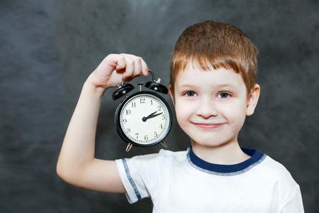 niños desayunando: Niño pequeño que sostiene un reloj de alarma. Foto de archivo