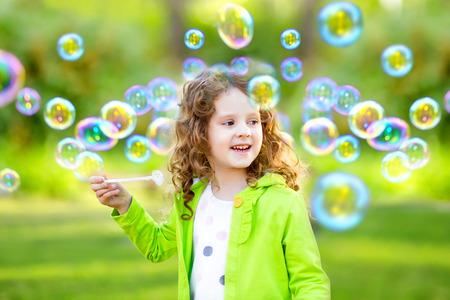 Een klein meisje blaast zeepbellen, lenteportret mooi krullend baby.