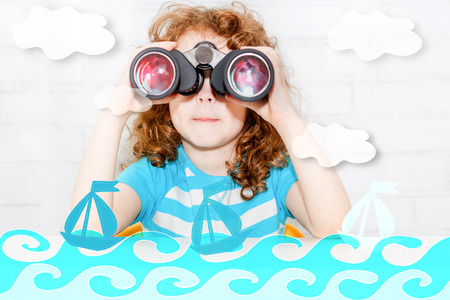 Little girl sitting at a table looking through binoculars photo